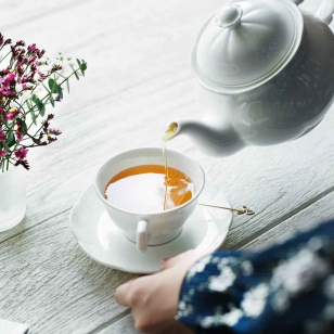 person holding white ceramic teapot and pouring tea in cup